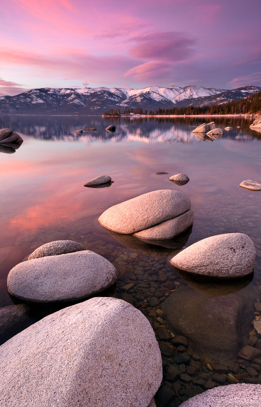 A pink sunsetover the clear waters and boulders of Sand Harbor in Lake Tahoe.