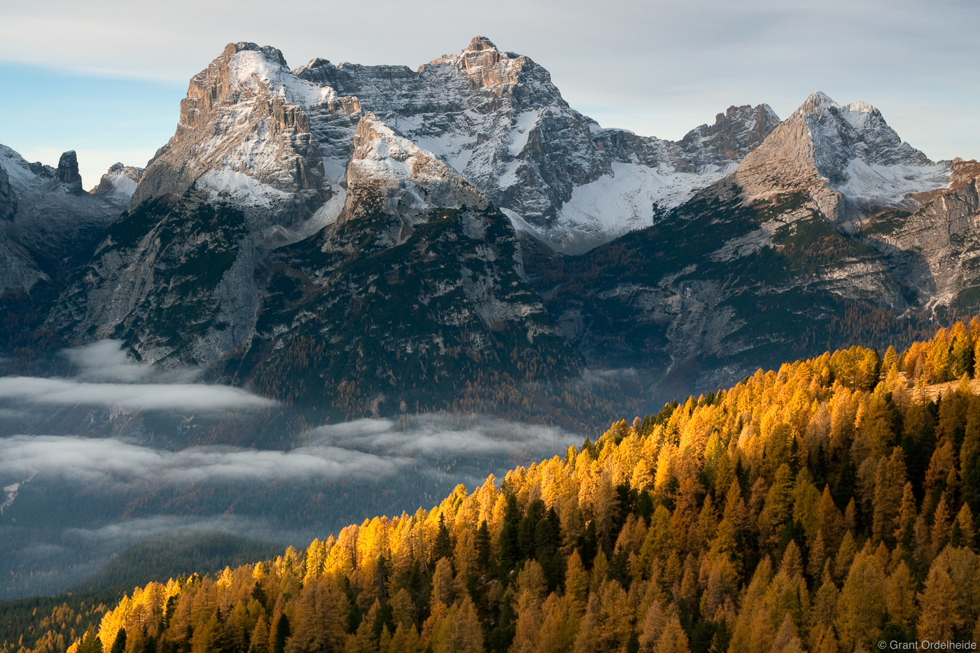 Early morning scene of clouds, larch trees, and the Sorapiss Group in the Dolomite Mountains.