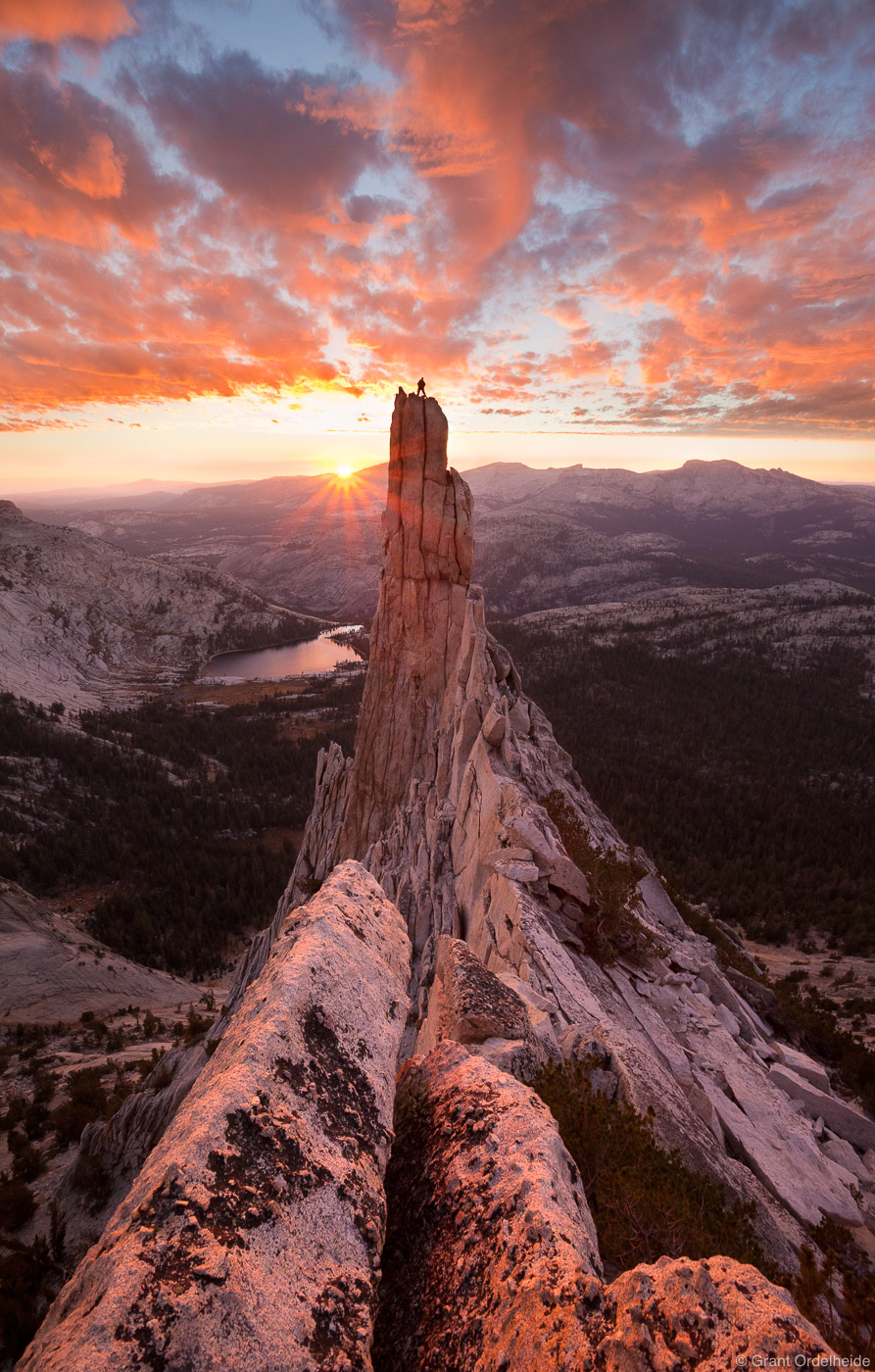 A climber stands atop the striking granite tower known as Eichorn Pinnacle. The pinnacle which lies on the western flank of Cathedral...