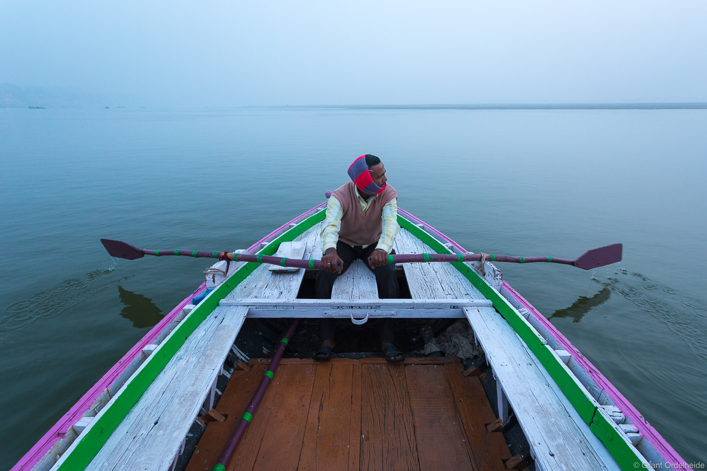 A man rows a boat on the holy Ganges River early on a foggy morning.