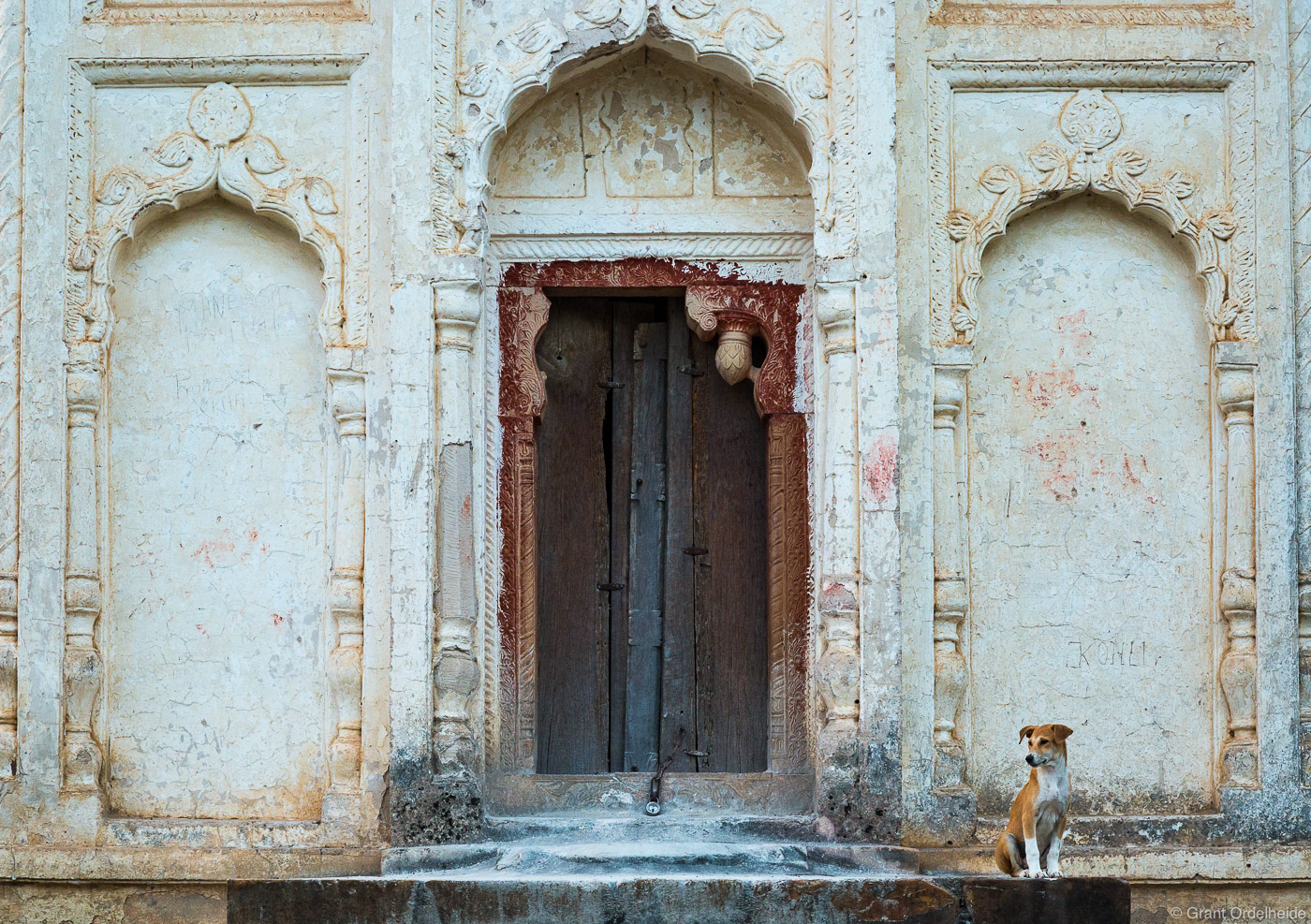 A stray dog stands guard at the entrance of one of the Lakshmana Temples.