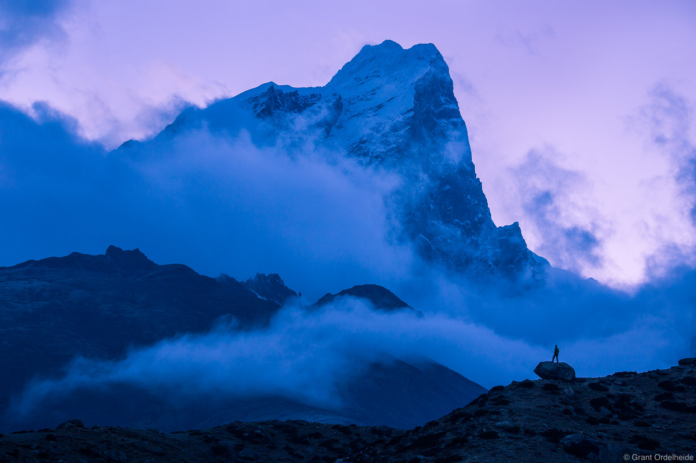 A silhouetted figure gives scale to the massive mountain Taboche as night falls in the Himalaya.