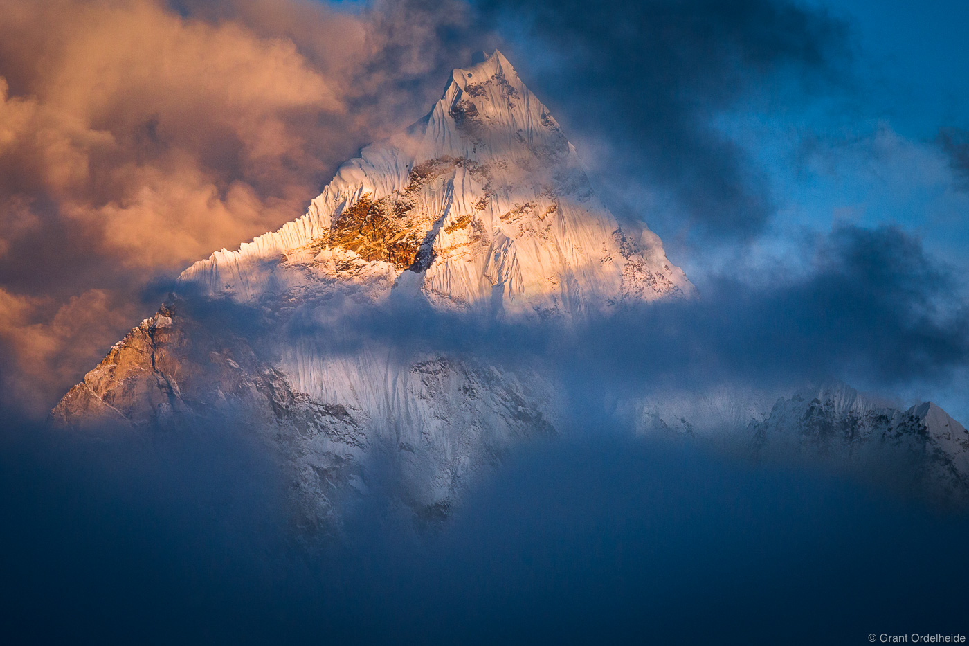 Ama Dablam peaks through the clouds in the Everest Region of Nepal's Himalaya.