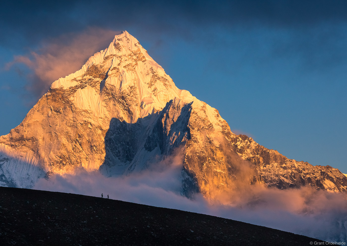 Two figures shrink in front of the massive Ama Dablam in Nepal's Everest Region.