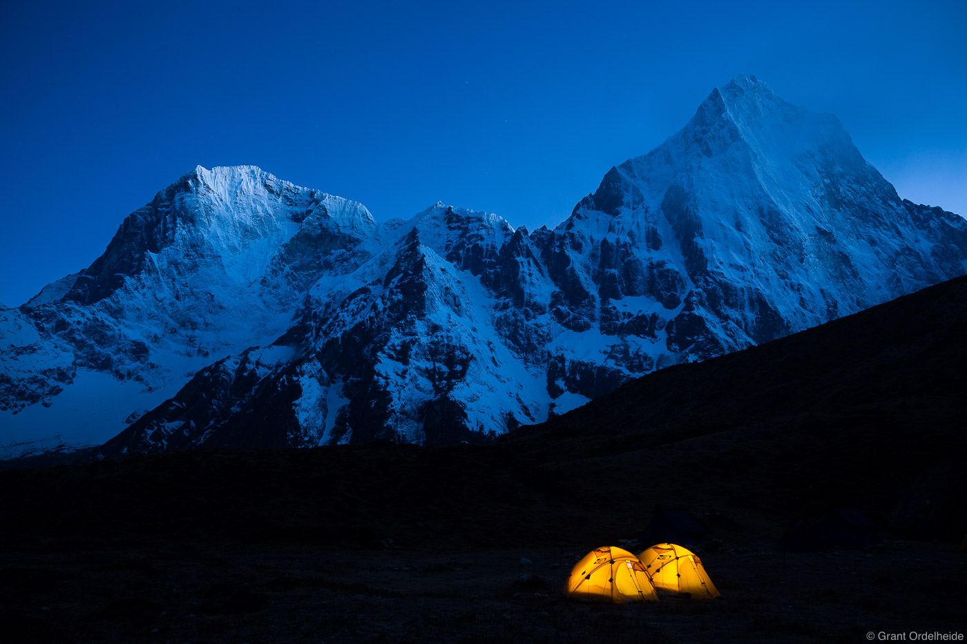 Two tents illuminated at Lobuche East basecamp with Taboche and Cholatse towering above them.