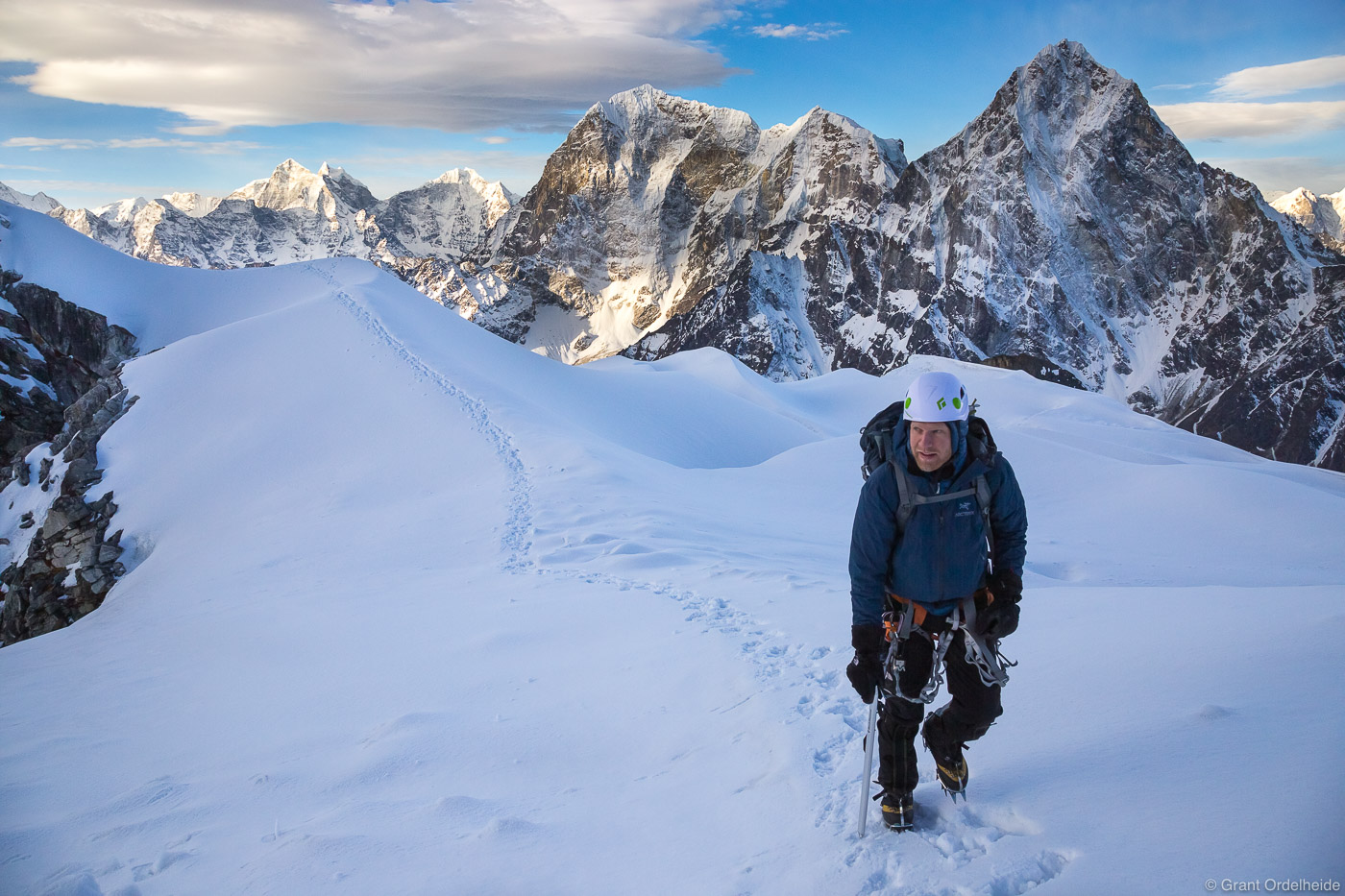 A climber  high on Lobuch East with Taboche and Cholatse in the background.