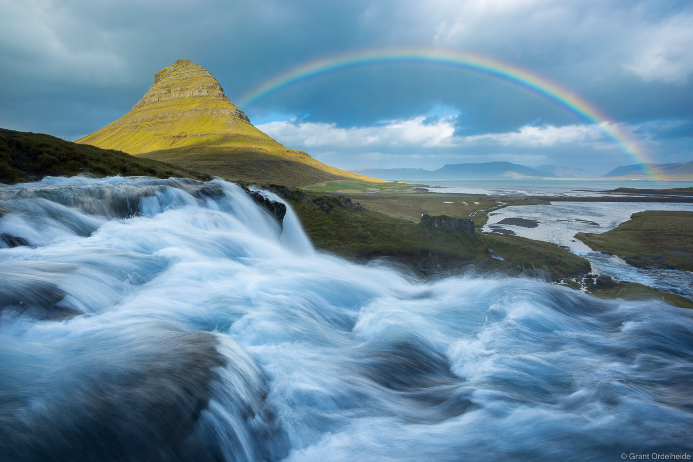 A rainbow over a waterfall and Kirkjufell mountain on theSnæfellsnes peninsula in western Iceland.
