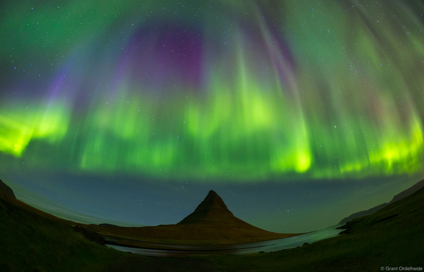 A colorful curtain of Aurora Borealis descends over Kirkjufell mountain on theSnæfellsnes peninsula in western Iceland...