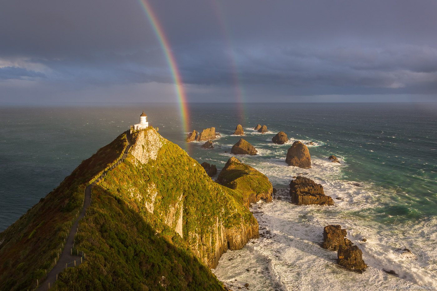 A rainbow over the Nugget Point Lighthouse along the coast of New Zealand's South Island.