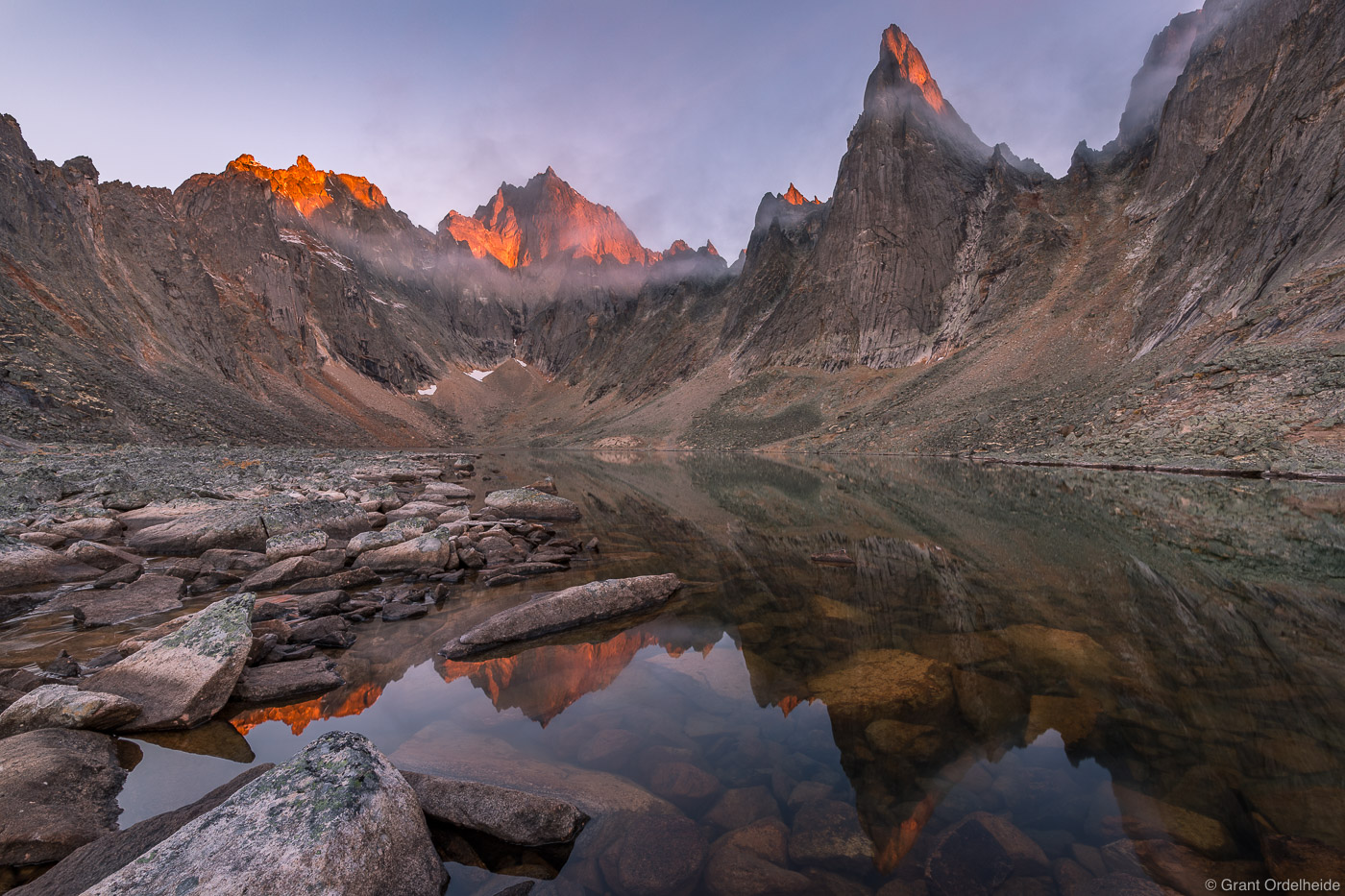 Sunrise over some rugged peaks from aremote lakein Tombstone Territorial Park.