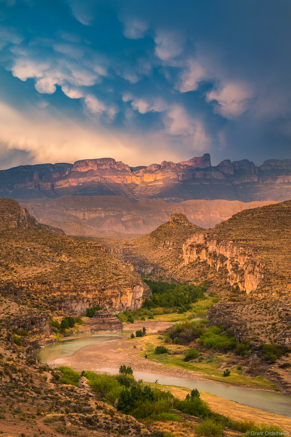 Storm light over the Rio Grande river and Sierra del Carmen Mountains viewed from Big Bend National Park.