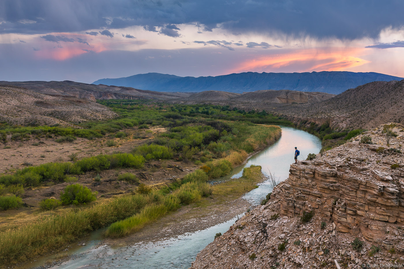 A hiker looks out into Mexico from above the Rio Grande river in Big Bend National Park.