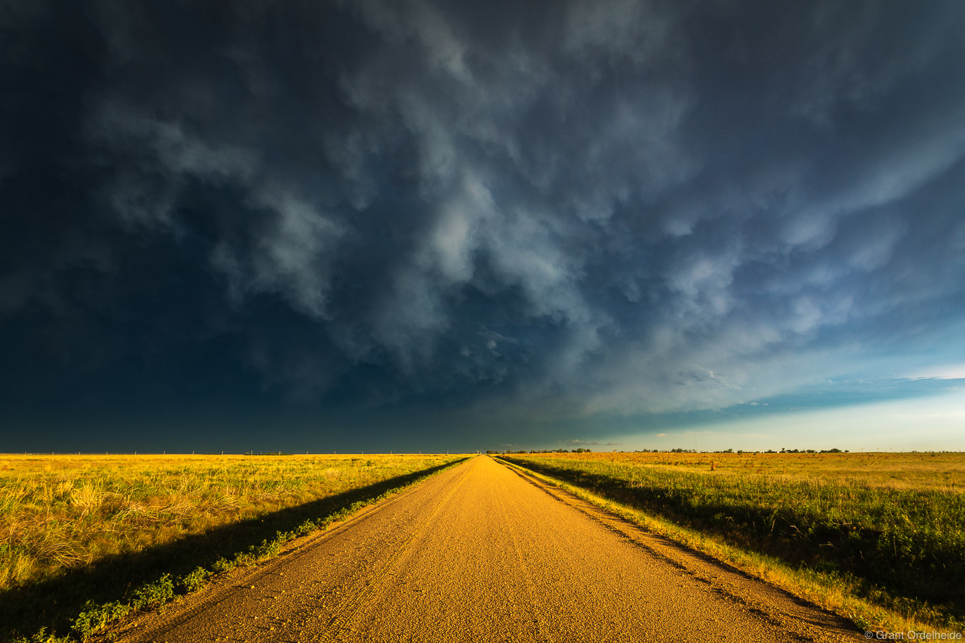 A thunderstorm at sunset over rural dirt road in Kansas.