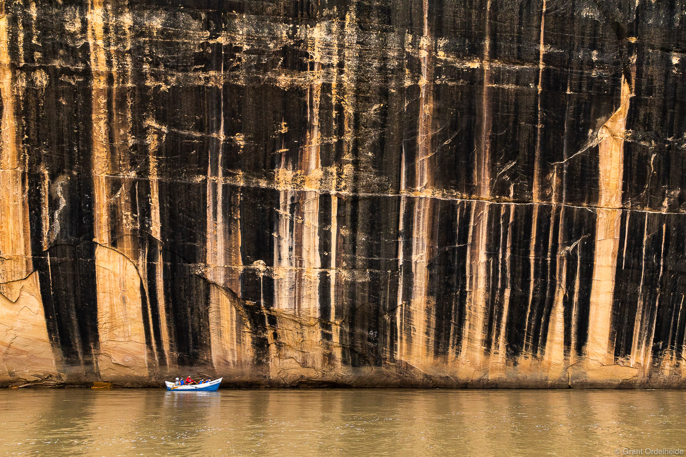 A dory boat passing below the Tiger Wall, a feature along the Yampa River in Dinosaur National Monument.