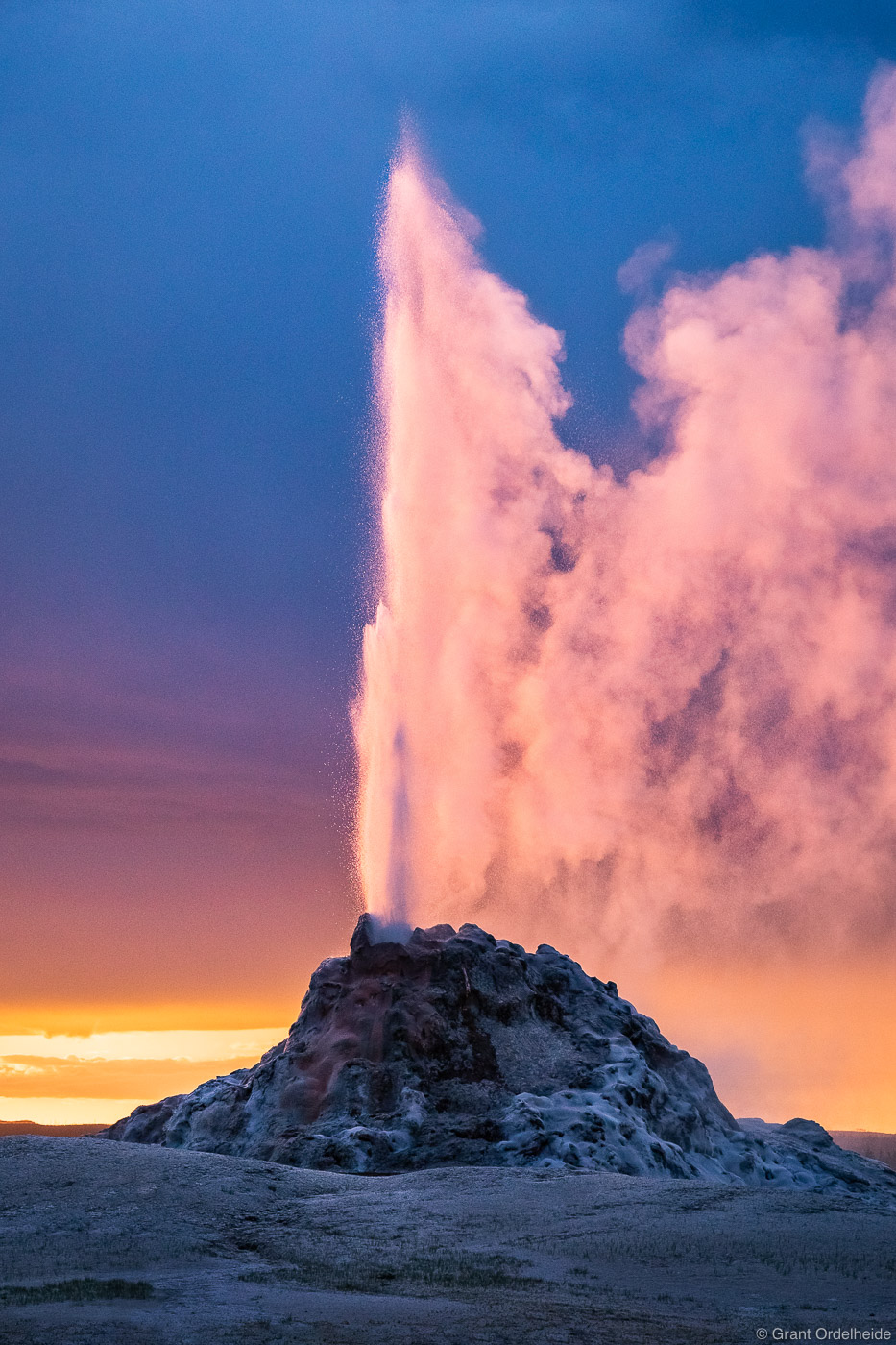 A stormy sunset over an erupting White Dome Geyser along Yellowstone's Firehole Lake Drive.
