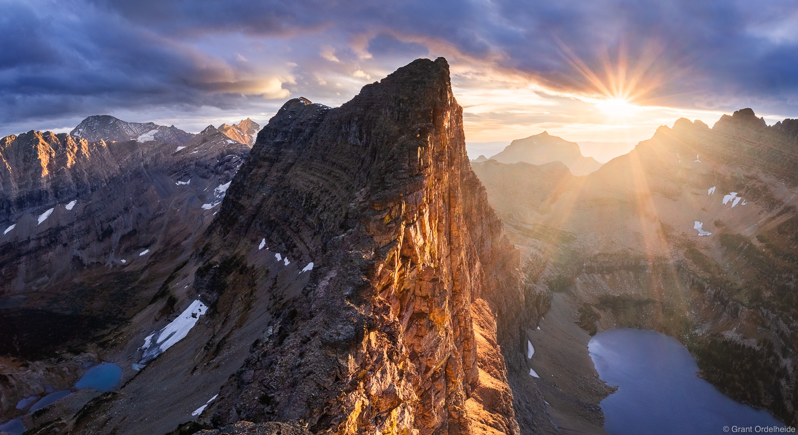 A stormy autumn sunset over the impressive Dragon's Tail formation in Glacier National Park.