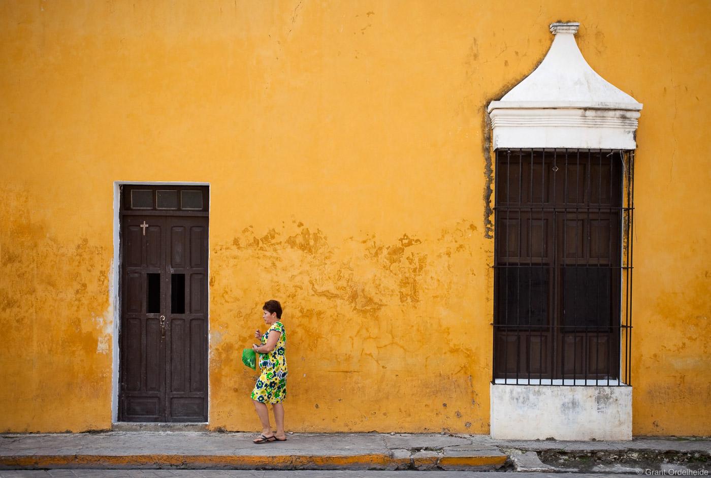 A woman walking down the streetin the yellow city of Izamal.