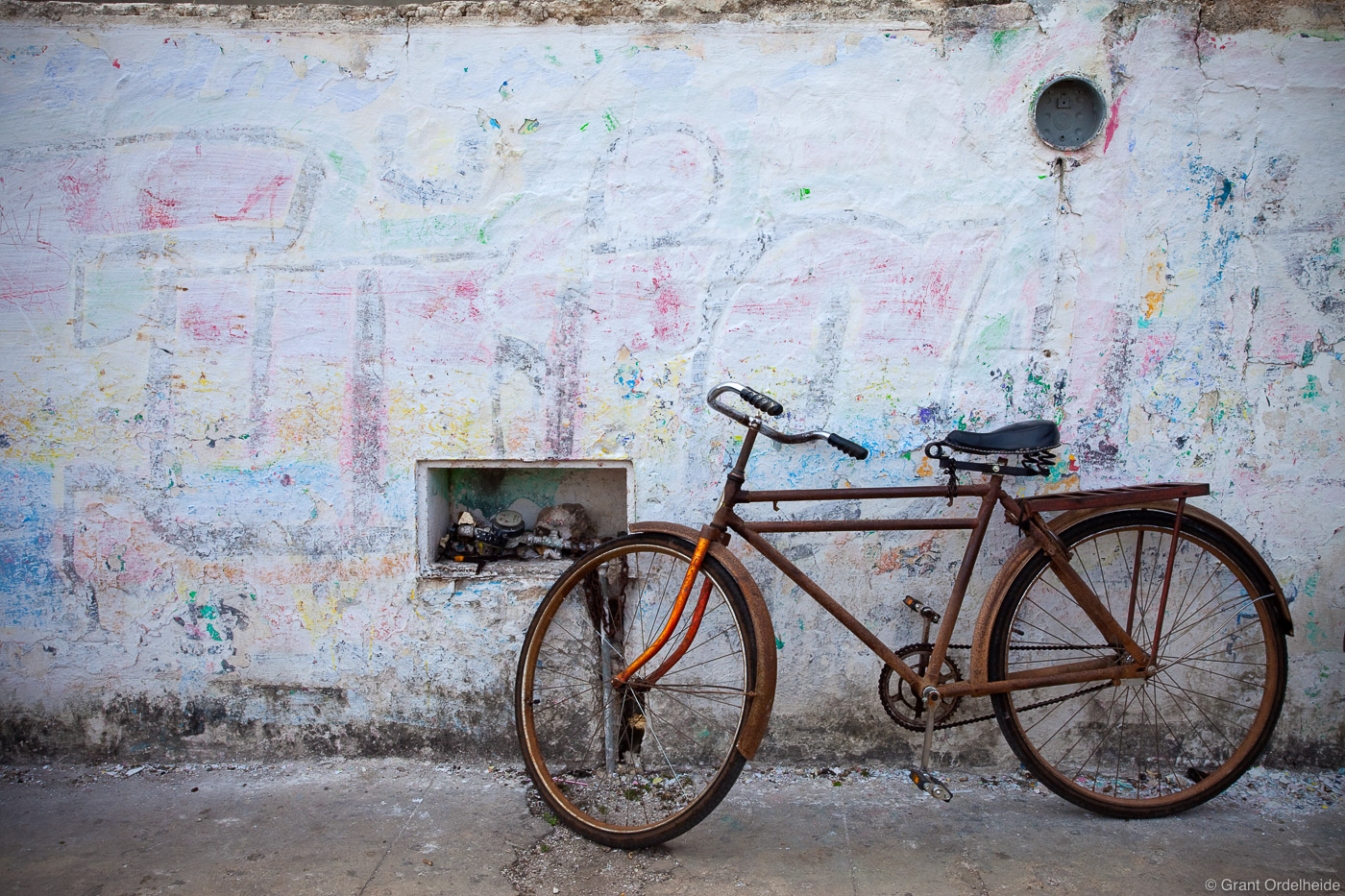 An old rusty bicycle in front of a faded wall.
